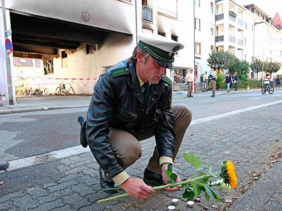 Ein Polizist legt in Lörrach am Tatort eine Blume nieder   | Foto: dpa
