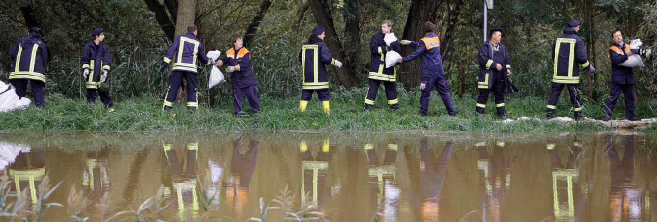 Feuerwehrleute sichern am Mittwochnach...en durchweichten Deich mit Sandsäcken.    Foto: dpa
