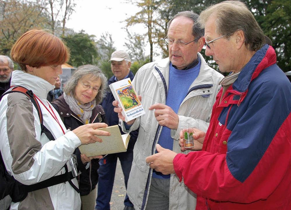 Rolf Langendörfer (Mitte) erklärt das  Schmiedledick-Buch.   | Foto: Umiger