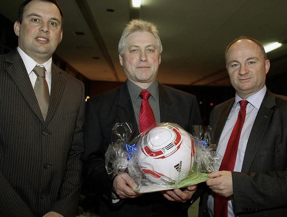Bernd Dosch (links)  und Dietmar Benz ...rsitzende Rudi Aman ein Geschenk mit.   | Foto: sandra decoux-kone