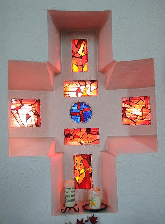 Leuchtend im Abendlicht: Das Fenster d...apelle nimmt die Kreuzform wieder auf.    Foto: Robert Bergmann