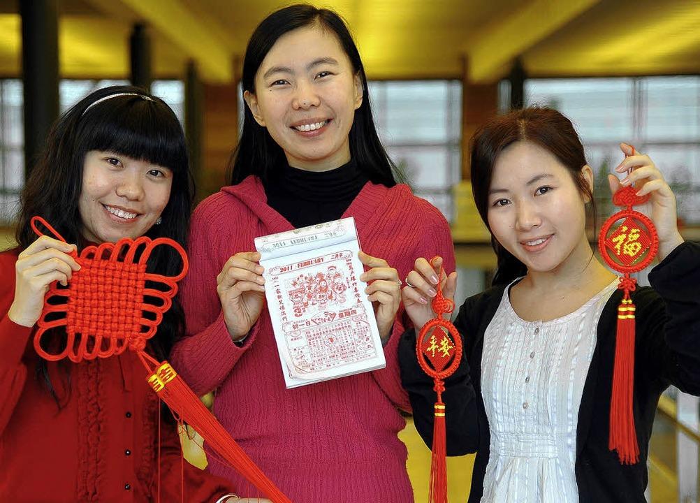 Ladies in red: Yuan Yang, Sen Yang und... (von links) mit Festdeko und Kalender  | Foto: Ingo Schneider