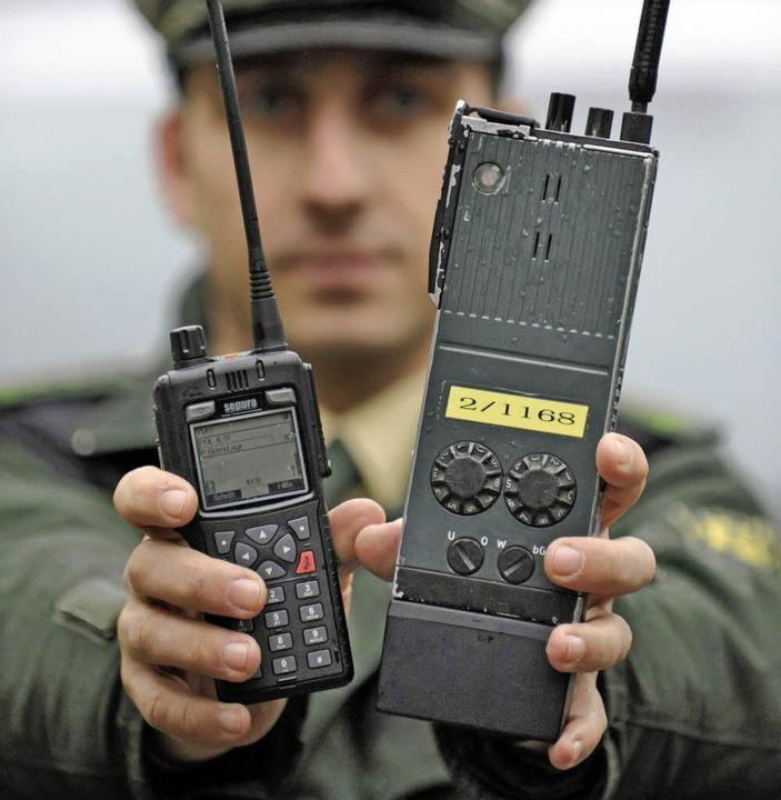 Digitalfunk: Ein Polizeibeamter hält i...oges  Polizeifunkgerät in den Händen.   | Foto: DPA