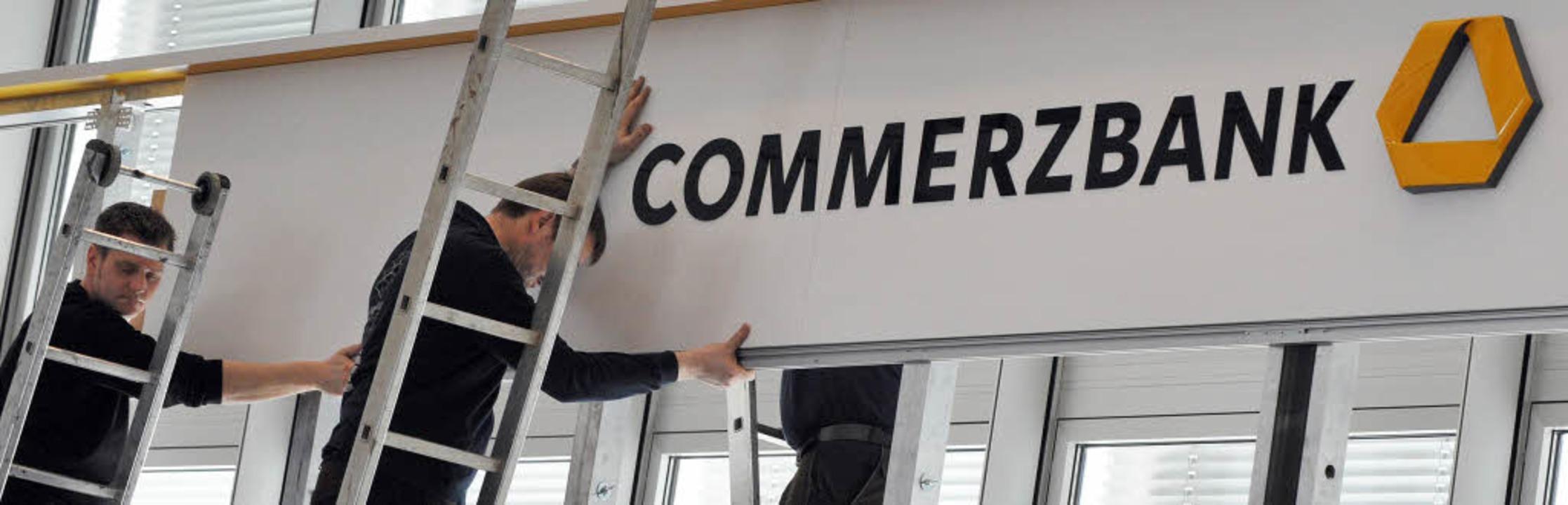 Jetzt wird abgebaut: Handwerker nehmen... Frankfurt das Logo des Konzerns ab.      Foto: dpa/dapd