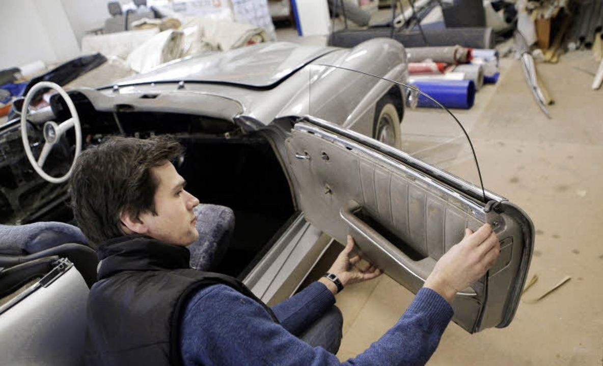 Ralf Herrenknecht arbeitet an der Lederverkleidung eines alten Mercedes.   | Foto: Christoph Breithaupt