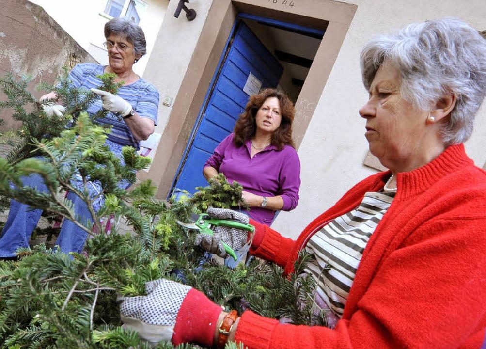 Maria Schiller, Carola Meier und  Anna....l.) binden Girlanden aus Tannengrün.     Foto: Michael Bamberger