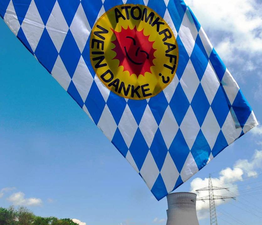 Eine bayerische Flagge mit Anti-Atom-L...eht vor dem AKW Gundremmingen im Wind.  | Foto: dpa