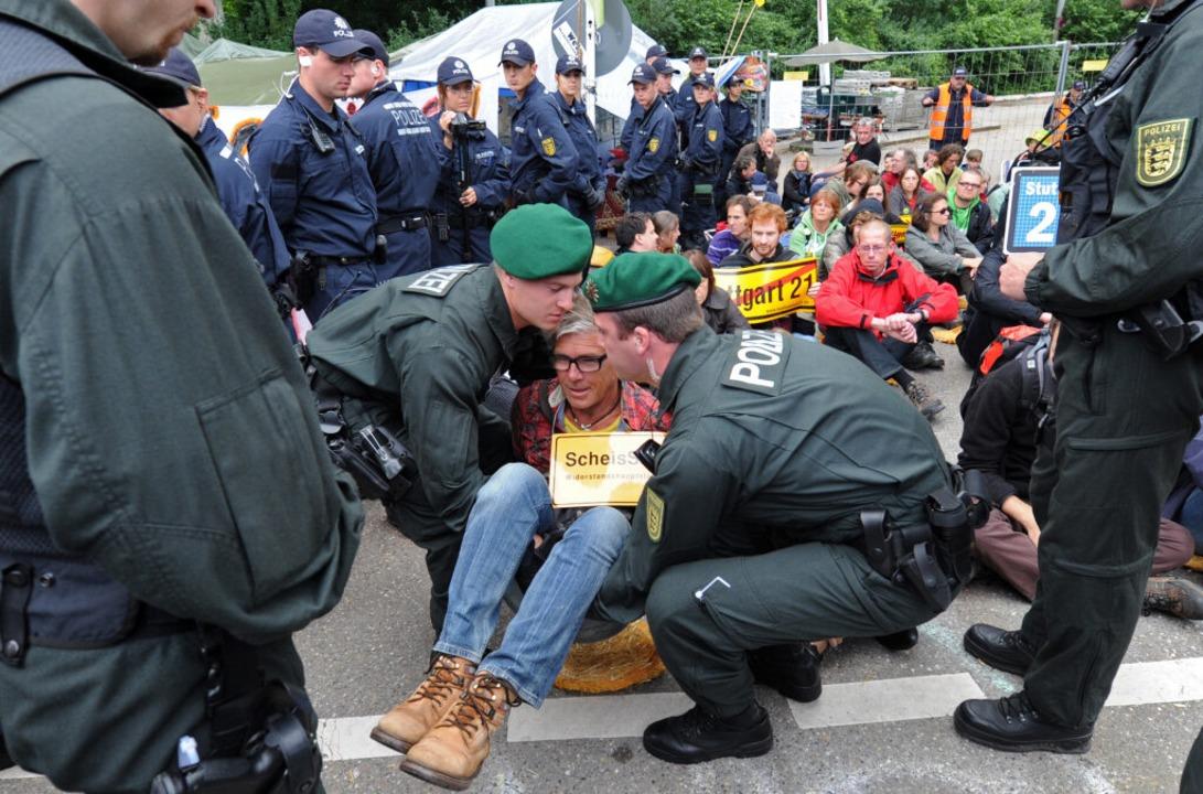Ein Stuttgart 21-Gegner wird am Dienst...em Bautor von der Polizei weggetragen.  | Foto: dpa