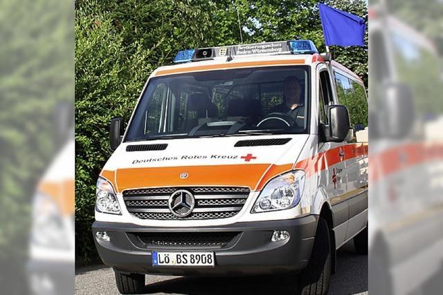 Rotes Kreuz mit blauer Fahne am weißen Auto
