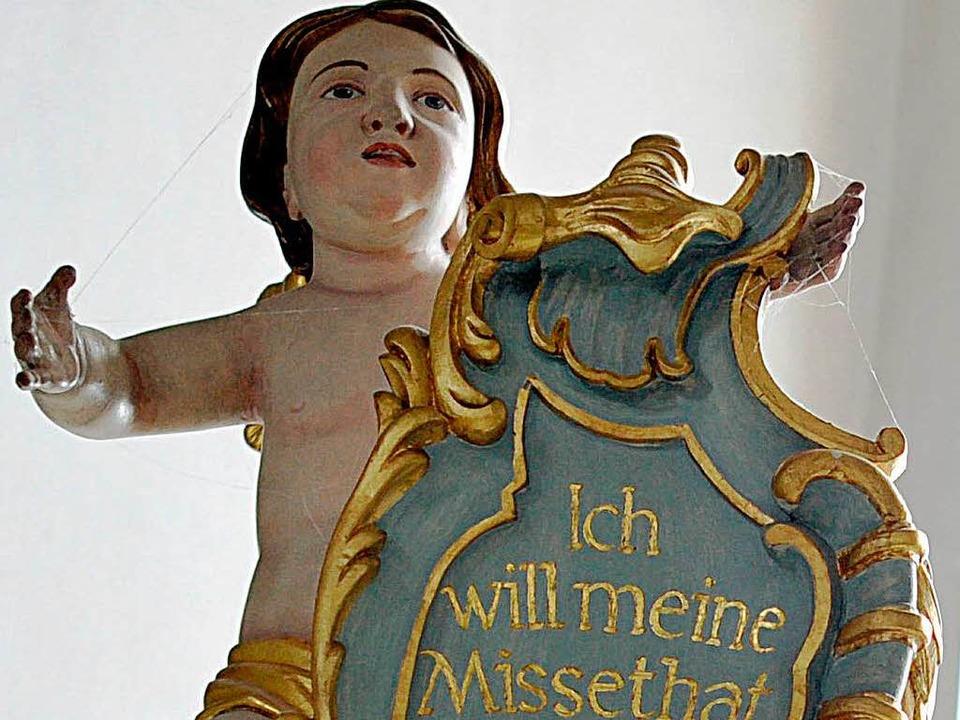 Ein Gotteskind  über einem Beichtstuhl...) hält eine Tafel mit einem Bußpsalm.   | Foto: dpa/dapd
