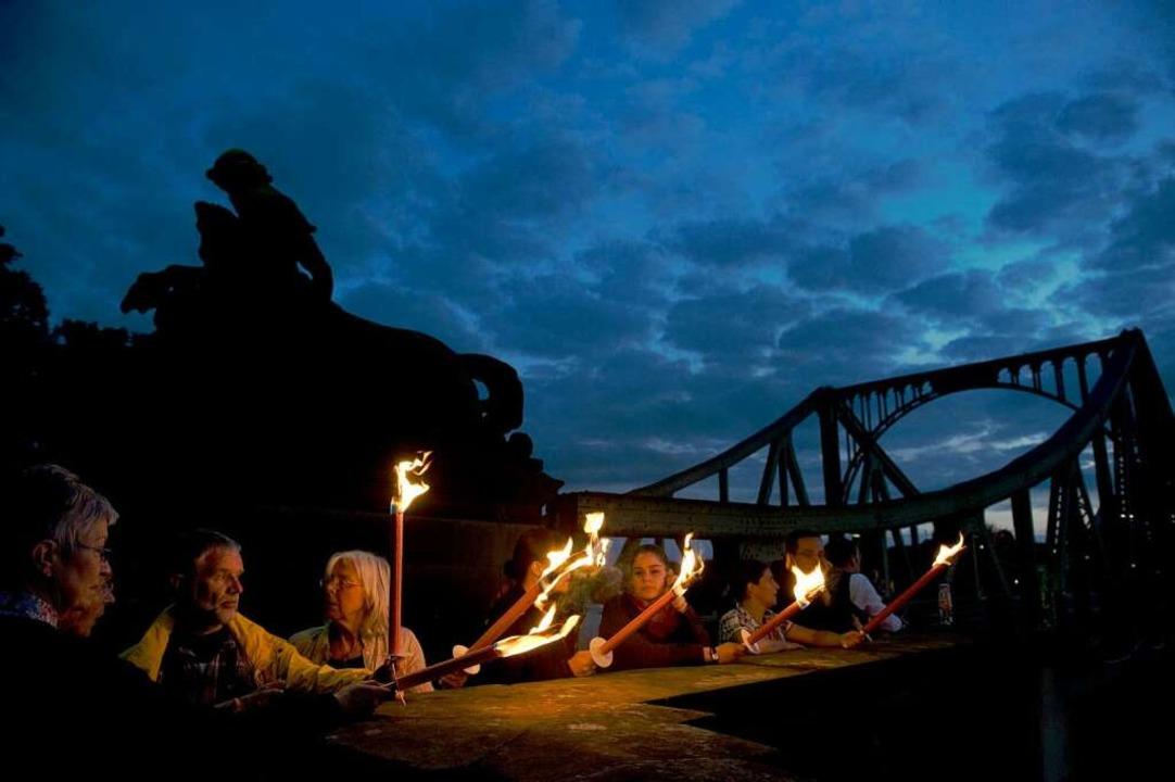 Teilnehmer der Lichterkette zum Gedenk...g an der Glienicker Brücke in Berlin.   | Foto: dapd/dpa