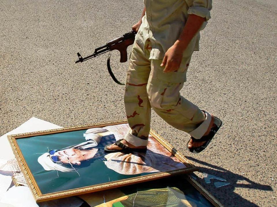 Ein bewaffneter Aufständischer tritt i...hrigen Machthabers Muammar al Gaddafi.    Foto: dapd
