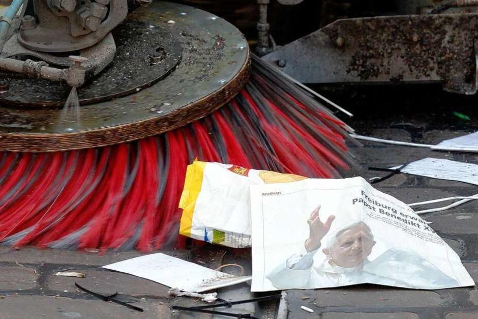 Eine Kehrmaschine beseitigt eine Zeitung mit dem Konterfei des Papsts. (Foto: dapd)