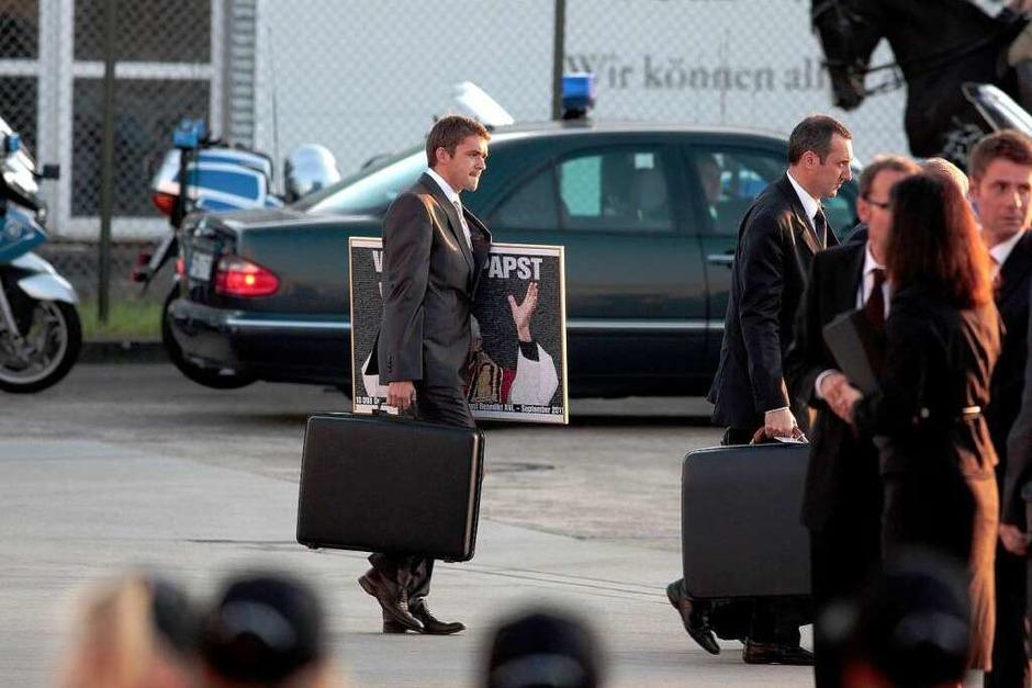 """Ein Mitarbeiter des Papstes trägt am Sonntag auf dem Flughafen in Lahr einen Koffer und eine Grafik aus mahr als 10.000 Einzelbildern, die die Schlagzeile der BILD-Zeitung """"Wir sind Papst"""" aus dem Jahr 2005 darstellt. Das Bild wurde Papst Benedikt XVI. von einem Vertreter der Deutschen Telekom als Geschenk überreicht. (Foto: Christoph Breithaupt)"""