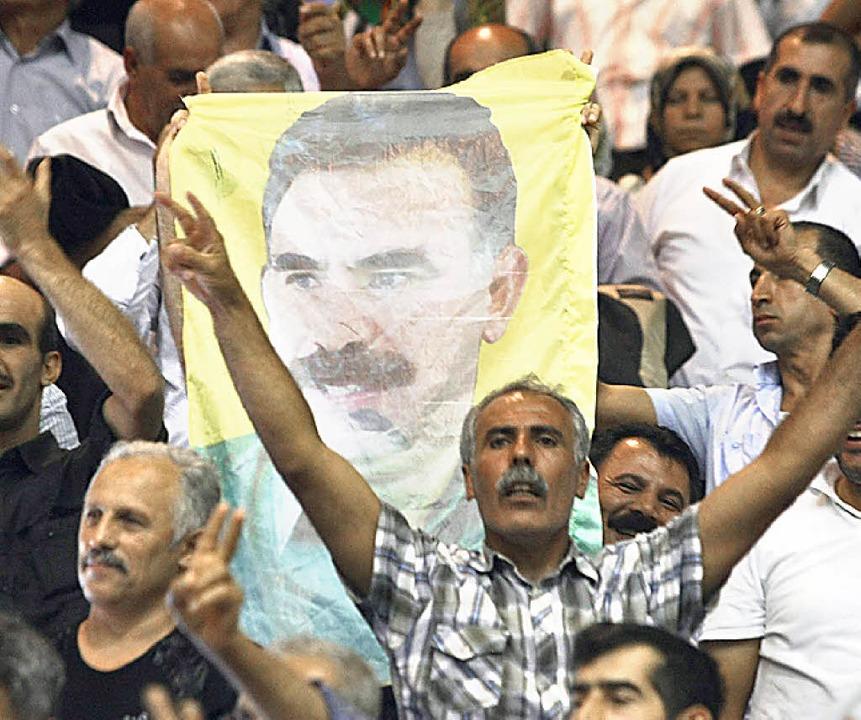 Kurden schwenken ein Bild von Öcalan.   | Foto: AFP