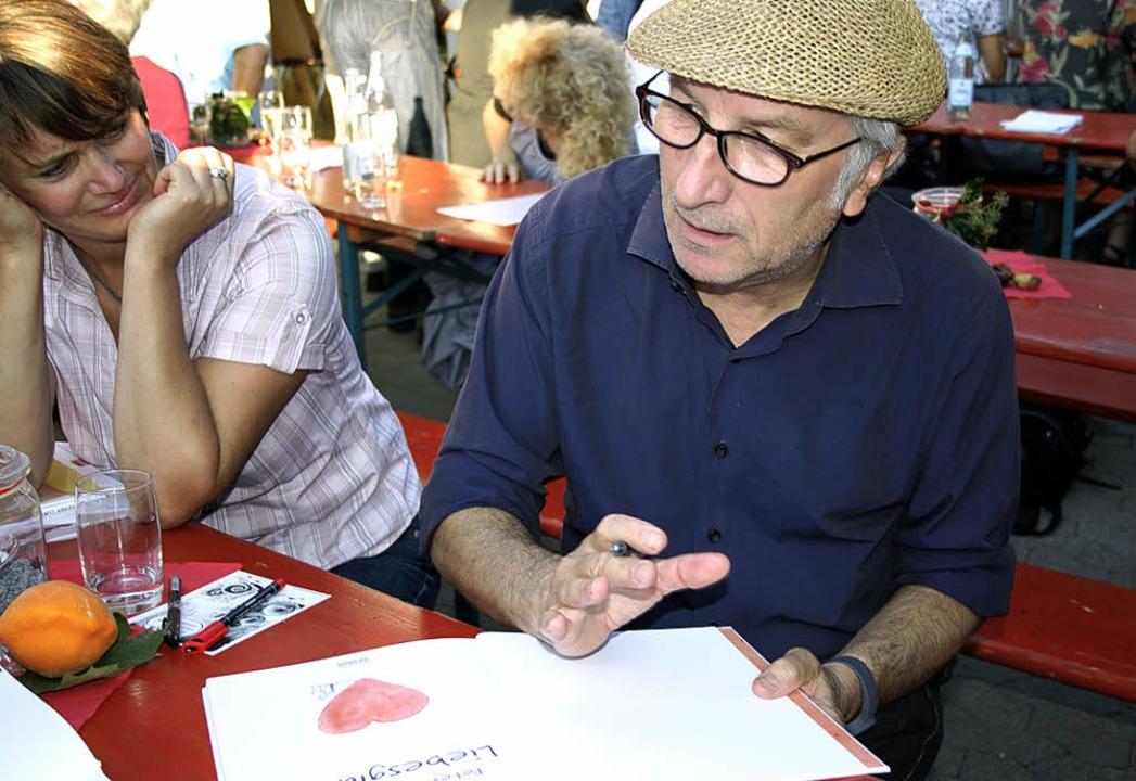 Cartoonist Peter Gaymann signiert seine Werke.
