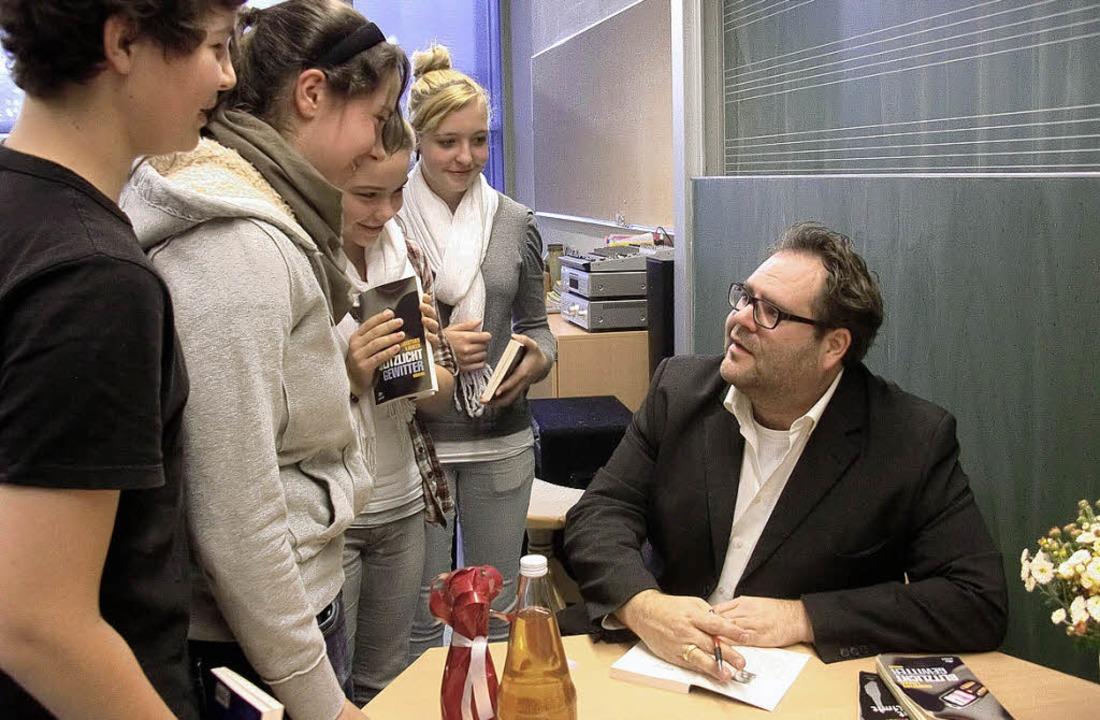 Christian Linker ist umringt von Schül...ngen ihr Buch signieren lassen wollen.  | Foto: Christiane Franz