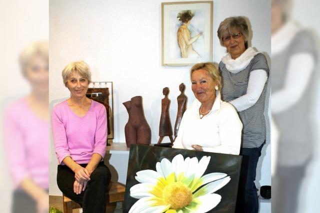 Drei Frauen zeigen Keramik und Bilder