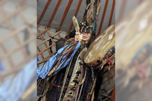 Ein Schamane zelebriert in einer mongolischen Jurte die Feuerzeremonie