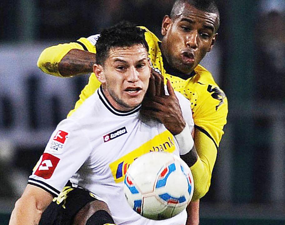 Dynamische Duell: der Gladbacher Bobadilla (vorn) gegen den Dortmunder Santana.  | Foto: afp