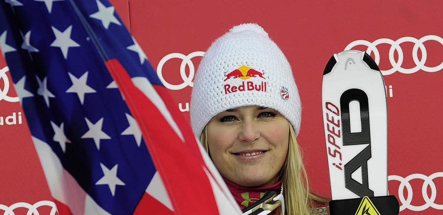 Eingerahmt von Nationalflagge und Skiern: Lindsey Vonn   | Foto: afp