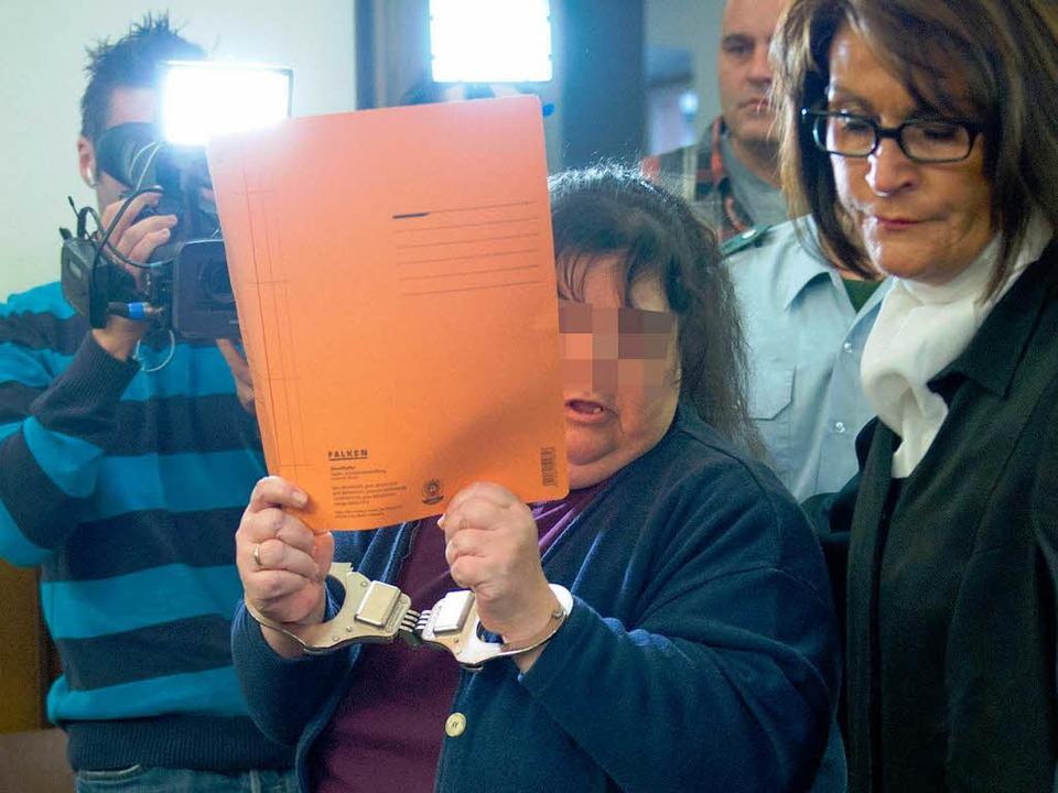 In Handschellen: Die 46-jährige Ehefra...Haupttäters am ersten Verhandlungstag.  | Foto: dpa