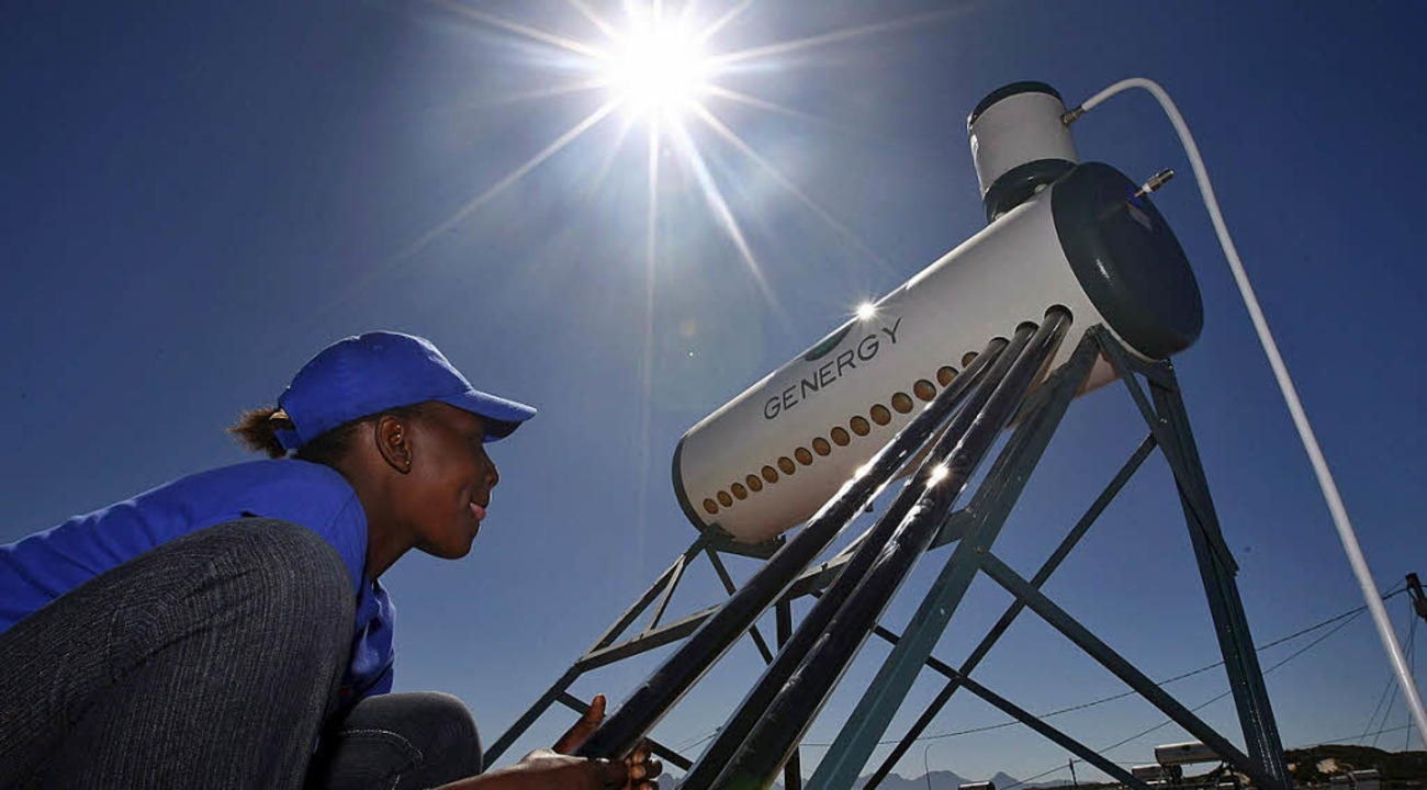 Eine Südafrikanerin installiert eine Solarwasserheizungsanlage.    Foto: dpa