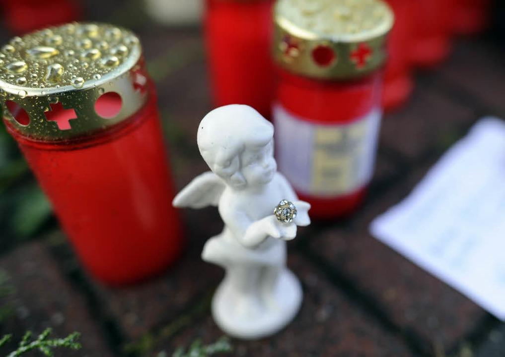 Blumen und Kerzen schmücken einen Bürg...eine 13 Jahre alte Tochter erschossen.  | Foto: dpa