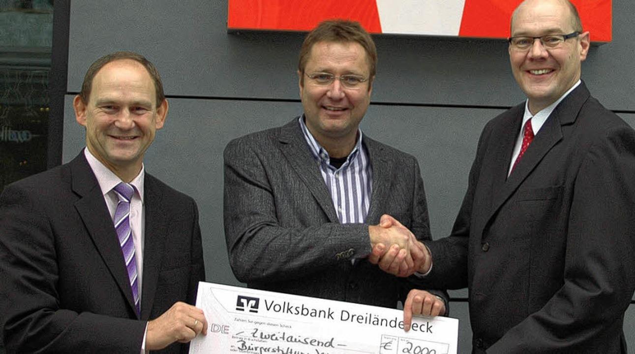Andreas Rühle (Bereichsleiter der Volk...nk, von links) bei  der Scheckübergabe  | Foto: Privat