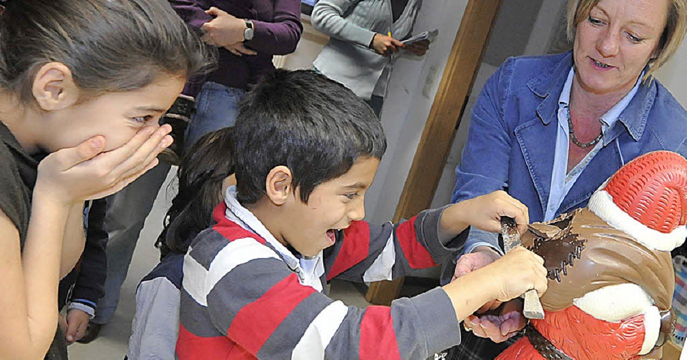 Süß und fröhlich: Kinder von St. Chris...der Riesenschokomann beim Anschneiden   | Foto: Michael bamberger