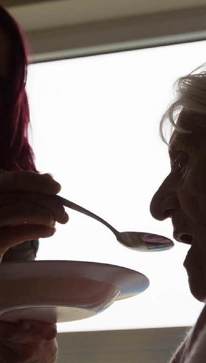Einer Seniorin wird in einem Alten- und Pflegeheim beim Mittagessen geholfen.     Foto: DPA