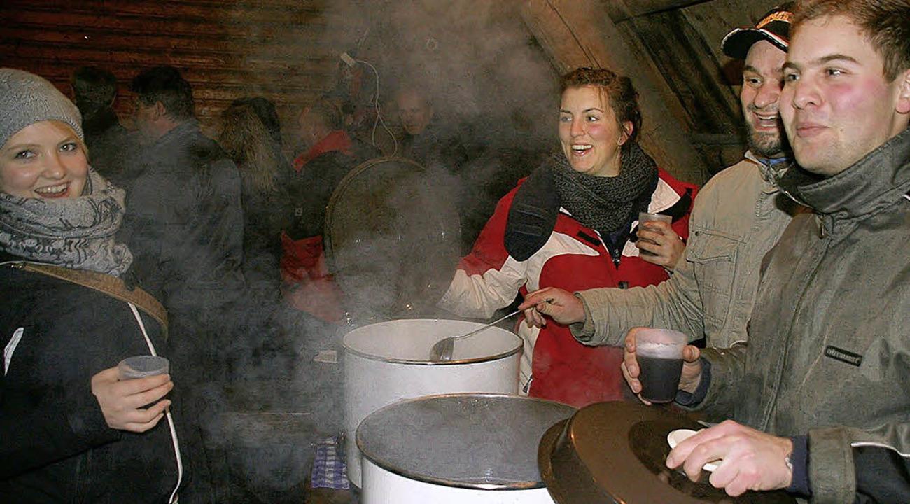 Gut gelaunt ließen sich die Gäste von ...n Gastgebern den Glühwein ausschenken.  | Foto: Peter Schütz
