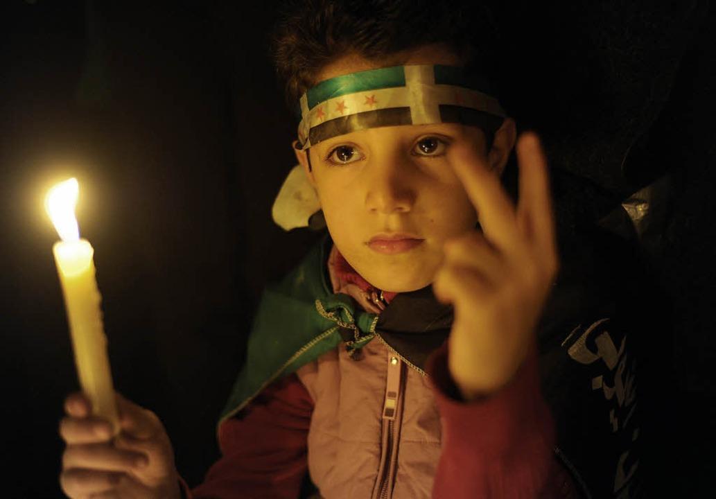 Ein syrischer Junge hält eine Kerze  f...chen Liga im ägyptischen Kairo statt.     Foto: dpa