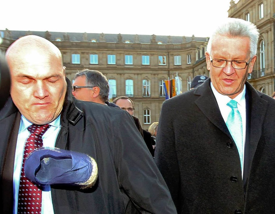Blauer Protest: Ein blauer Schlappen t...dnt Kretschmann (rechts) an der Brust.  | Foto: dpa