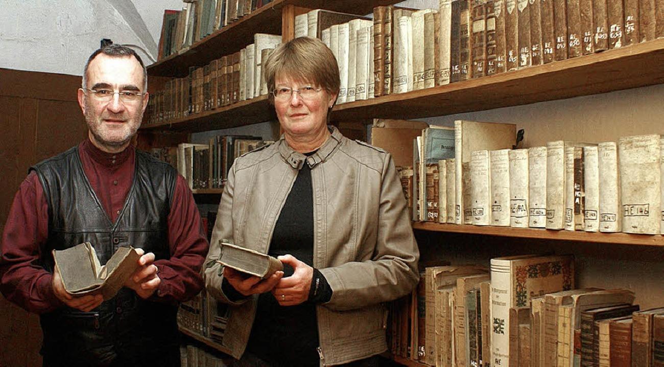 Doris Haspra und Pfarrer Peter Grüter zeigen die Schätze der Stiftsbibliothek.   | Foto: Valentin Zumsteg