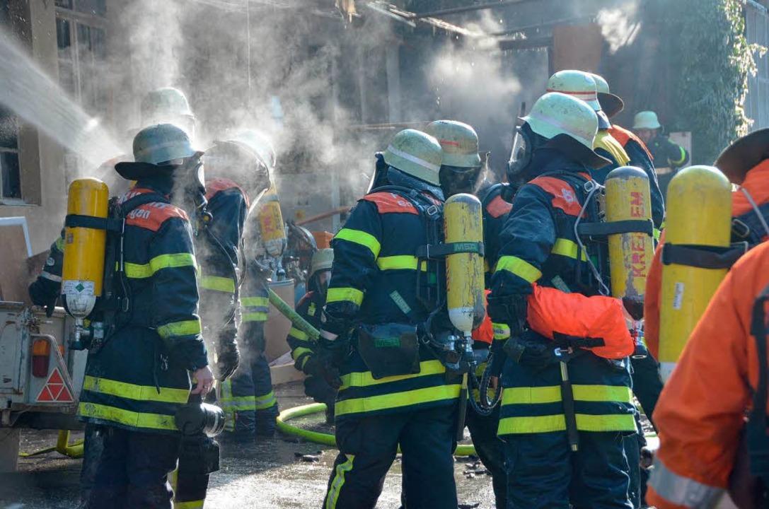 Helfer unter Atemschutz drangen ins Innere des brennenden Gebäudes ein.    Foto: Gerhard Walser