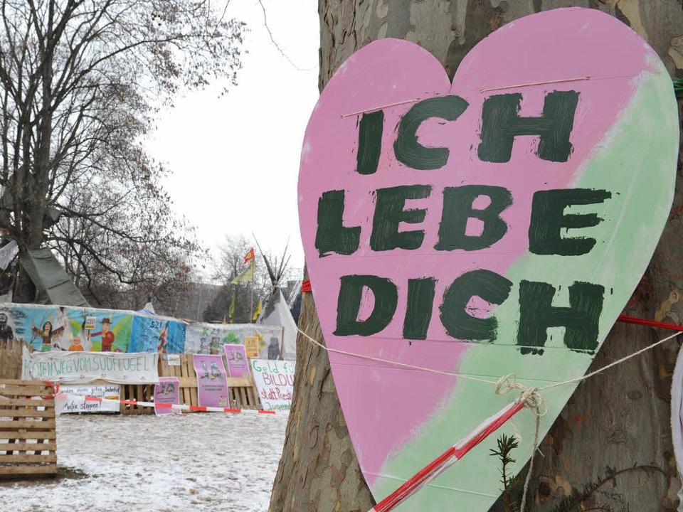 Ein herzförmiges Schild mit der Aufsch... in Stuttgart an einem Baum befestigt.  | Foto: dpa
