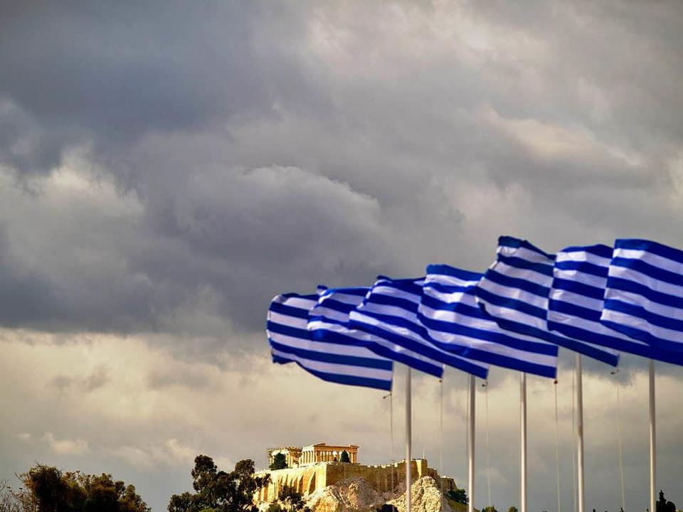 Griechische Fahnen wehen in Athen vor der alten Stadtfestung Akropolis.     Foto: dpa/dapd