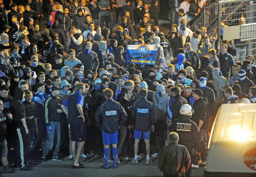 Karlsruher Fans belagern nach dem 2:2 ...d diskutieren mit Karlsruher Spielern.  | Foto: dpa