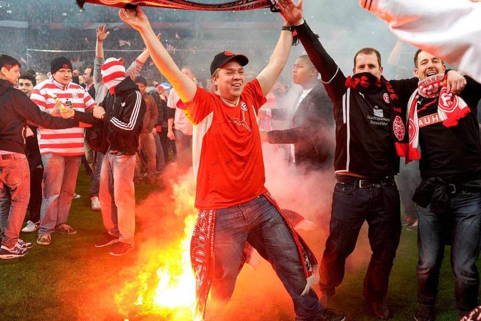 Die Partie in der Esprit-Arena stand in der Nachspielzeit am Rande des Abbruchs, weil Hunderte von Fans auf den Rasen gestürmt waren. (Foto: AFP)
