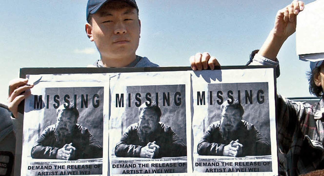 Ein chinesischer Demonstrant mit einem Flyer von AiWeiwei   | Foto: dpa