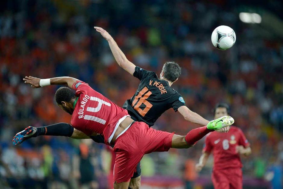 Zweifache Waage:   Robin van Persie (rechts) und Rolando im Vorrundenspiel Holland – Portugal: (Foto: AFP)