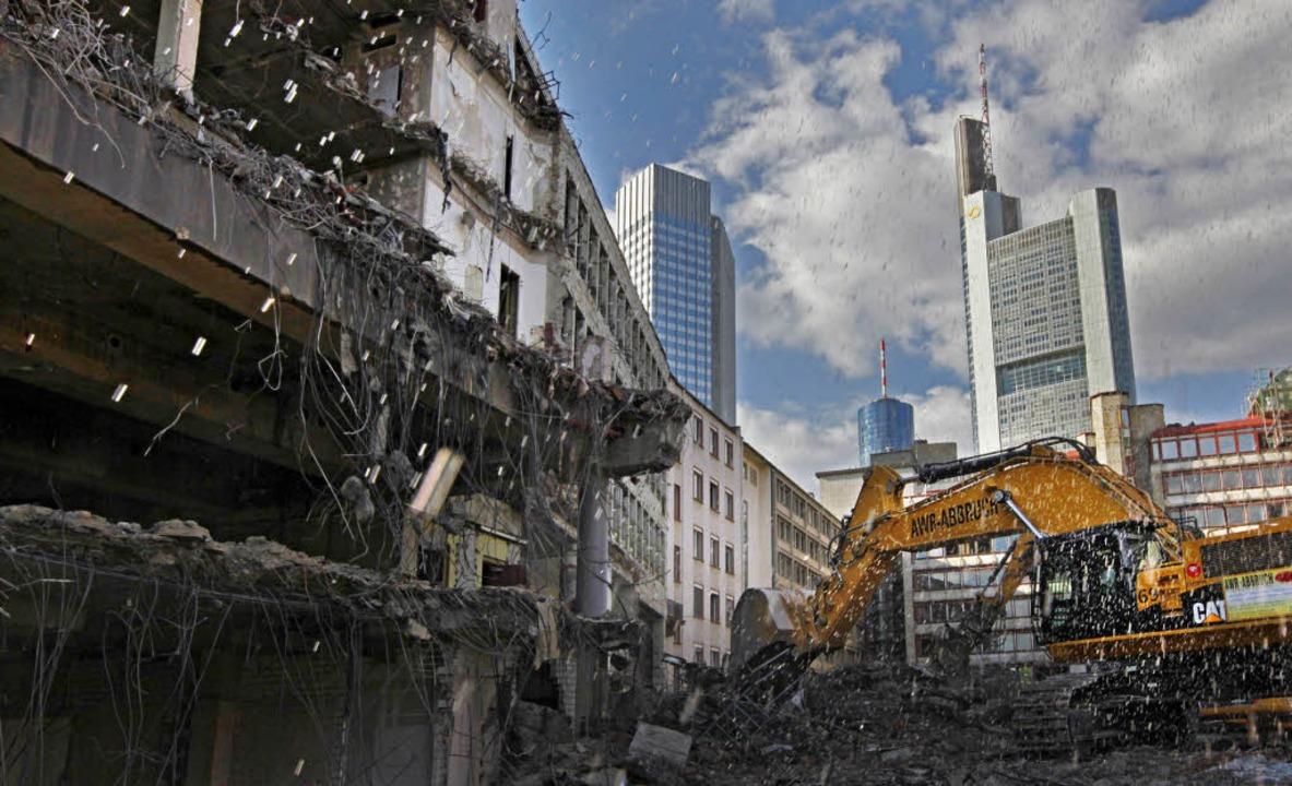 Szene mit Symbolkraft: Ein Bagger reiß...äude in Frankfurts Bankenviertel ab.    | Foto: dapd