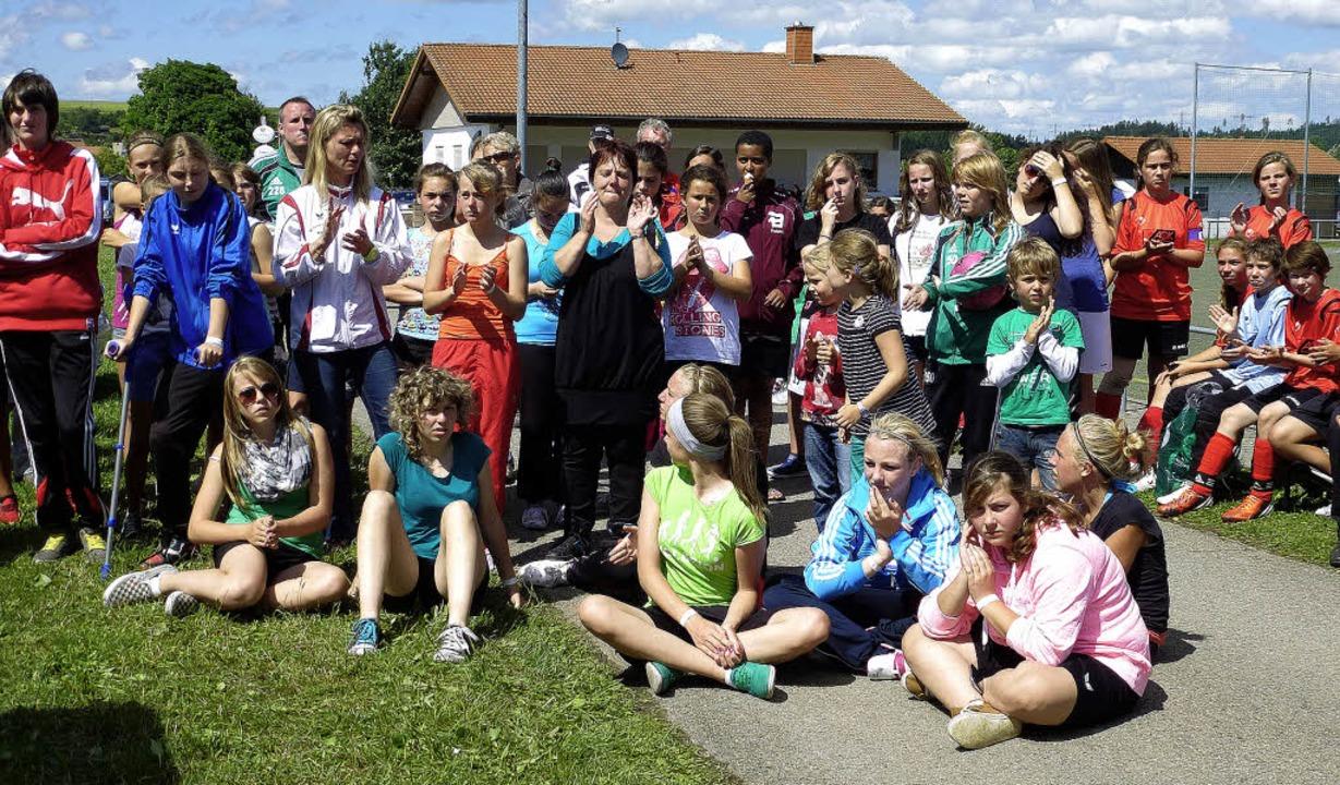 Die Mädchen warten nach den Strapazen des Fußballturniers auf die Siegerehrung.     Foto: Karla Scherer