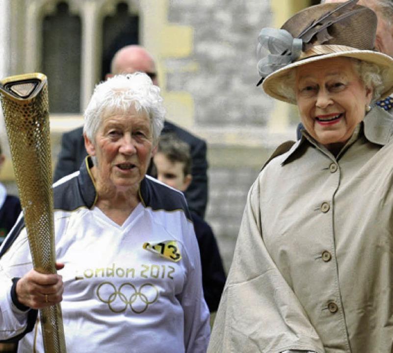 Die Queen (rechts) und eine Fackelläuferin     Foto: dapd