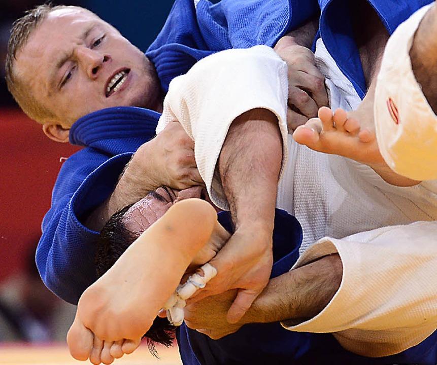 Dimitri Peters hat seinen usbekischen Gegner Ramziddin Sayidov fest im Griff.  | Foto: afp