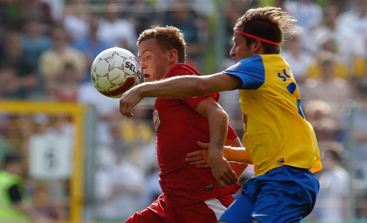 Victorias Jan Lauer und Freiburgs Max Kruse kämpfen um den Ball.  | Foto: dapd