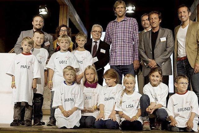 Dirk Nowitzki überreicht Freiburger Schülern einen 10.000-Euro-Scheck