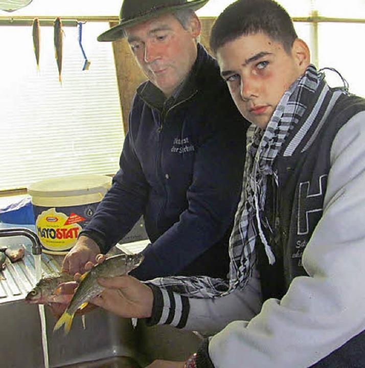 Werner Lämmlin (links) zeigt, wie man den Fisch richtig abschuppt und säubert.   | Foto: Albert Greiner