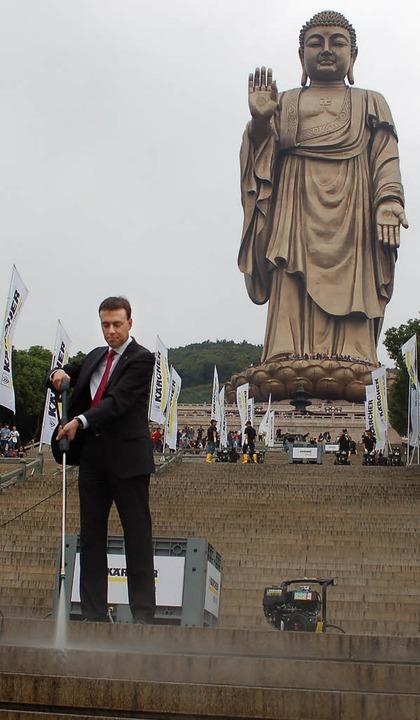 Nils Schmid macht mit einem Hochdruckr...gen Buddha-Statue in Lingsnan sauber.     Foto: hup